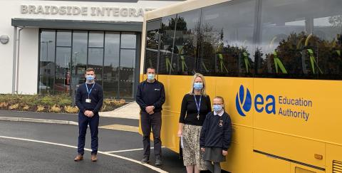 Photo of EA Bus with members staff and students wearing face masks  at Braidside Integrated PS Ballymena